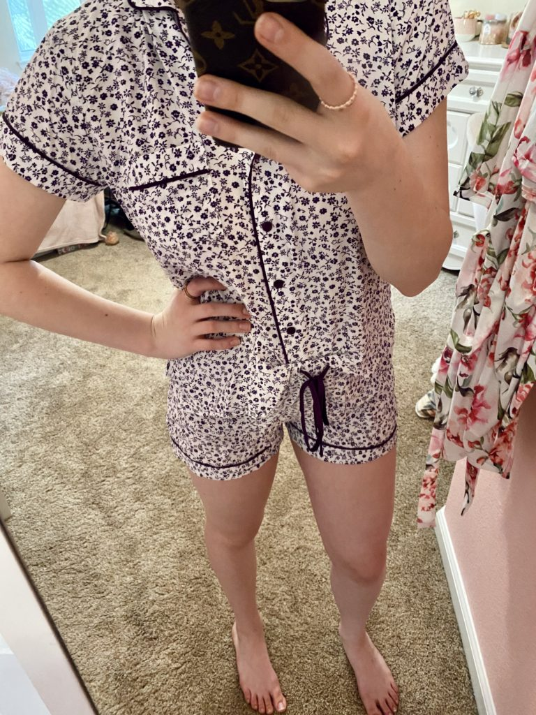 comfy essentials, dark purple and white ditsy floral pajama loungewear set for summer with a tie waist, button front collared design, and a shirt pocket with rose gold rings for a lounge look