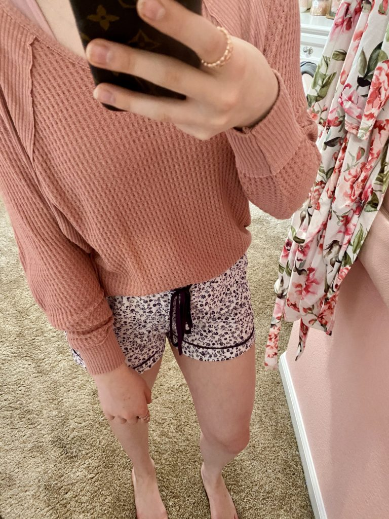 comfy essentials, pink waffle knit long sleeve top with purple and white ditsy floral pajama shorts, and a rose gold ring set for a comfortable and chill around the house look