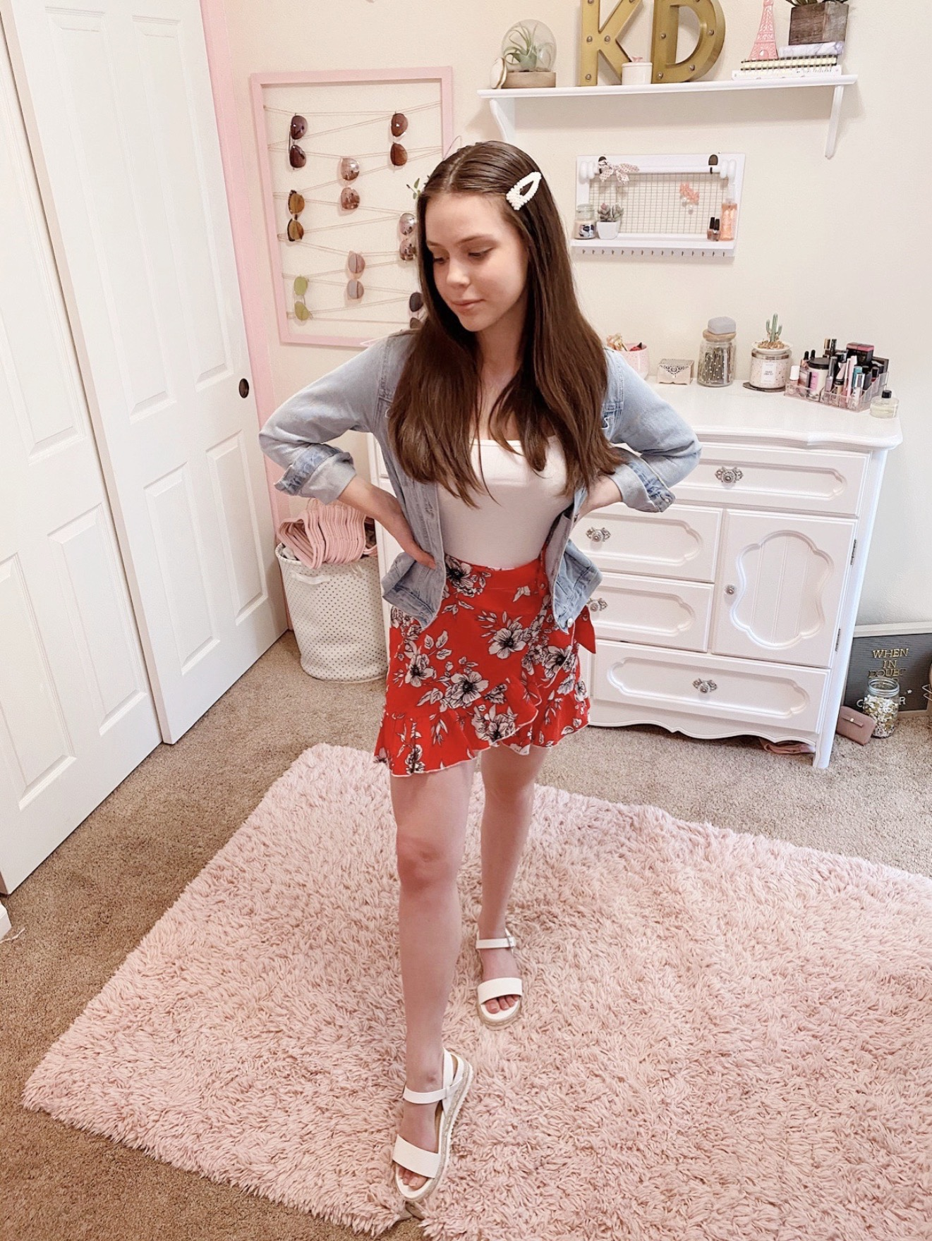 fourth of july outfit ideas, red floral wrap ruffle skirt with white straw espadrille sandals, a white cami ribbed bodysuit, a light wash distressed denim jacket, and pearl hair clip