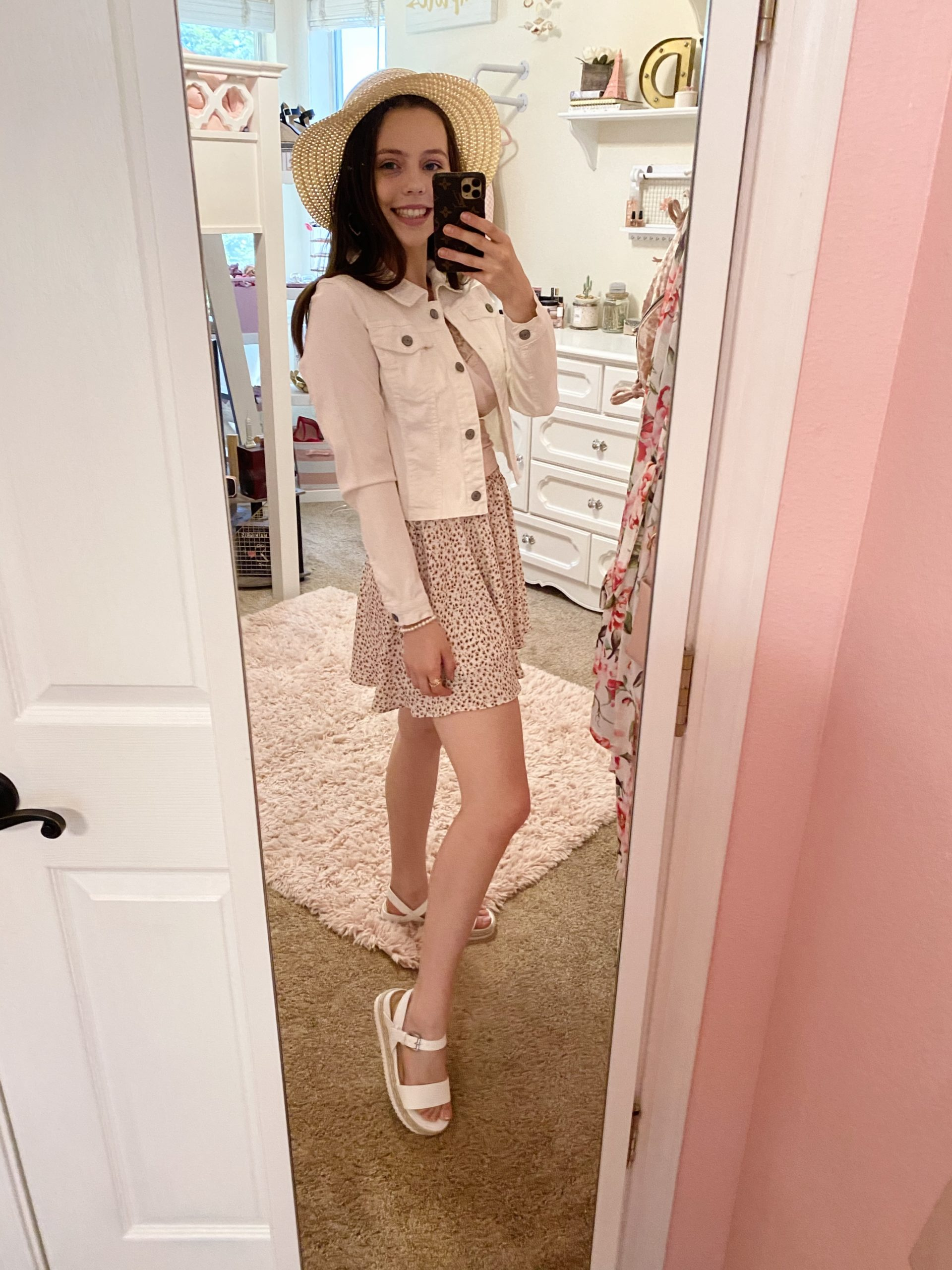 pink floral skirt outfit ideas, pink and white ditsy floral skirt styled with a blush lace tank top, a white cropped denim jacket, white straw espadrilles, a pearl bracelet, and a pink bow straw hat