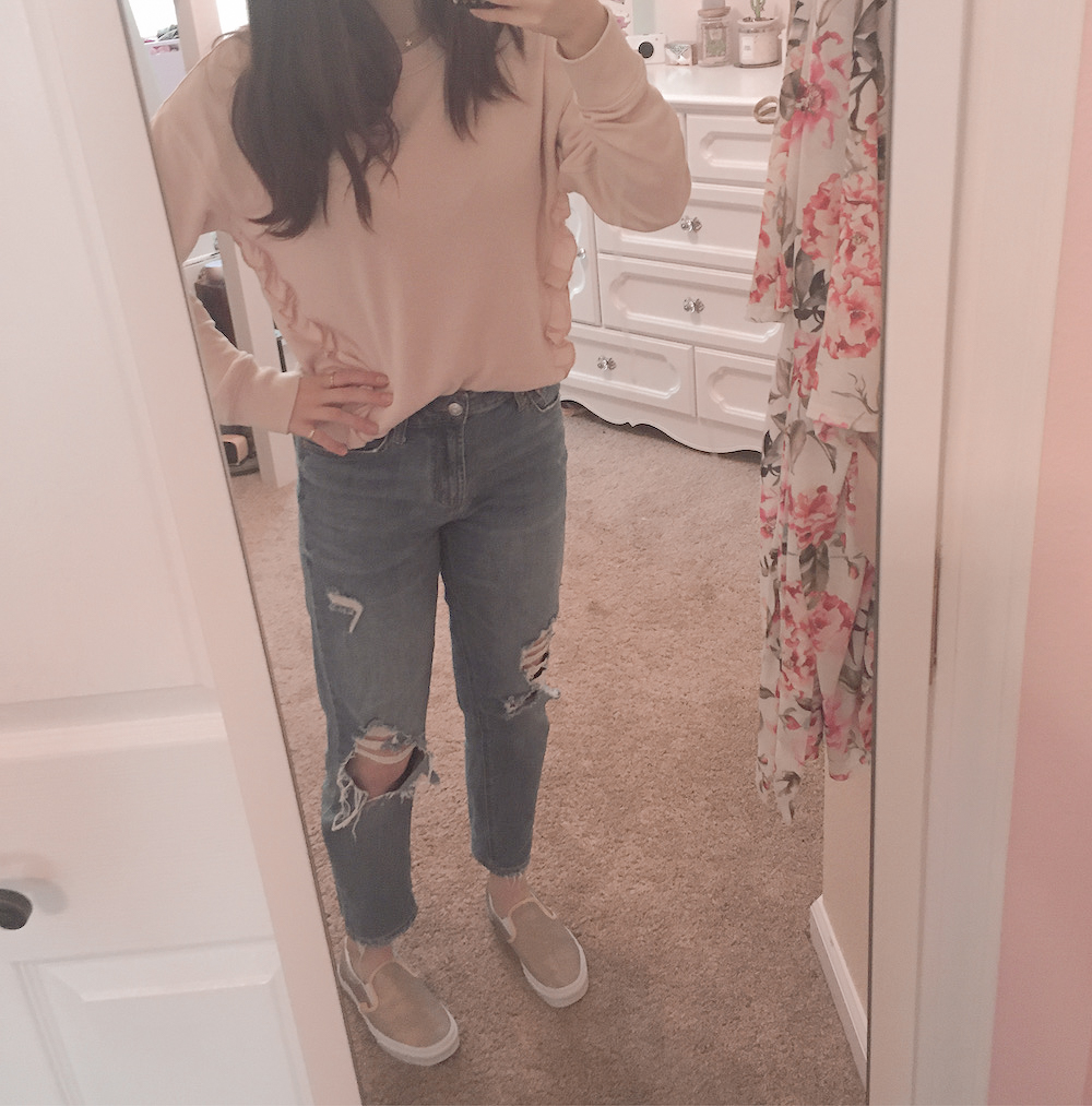 ripped mom jeans outfit ideas #1, mirror picture of girly girl wearing medium wash mom jeans styled with a ruffled pink sweatshirt and rose gold slip on vans