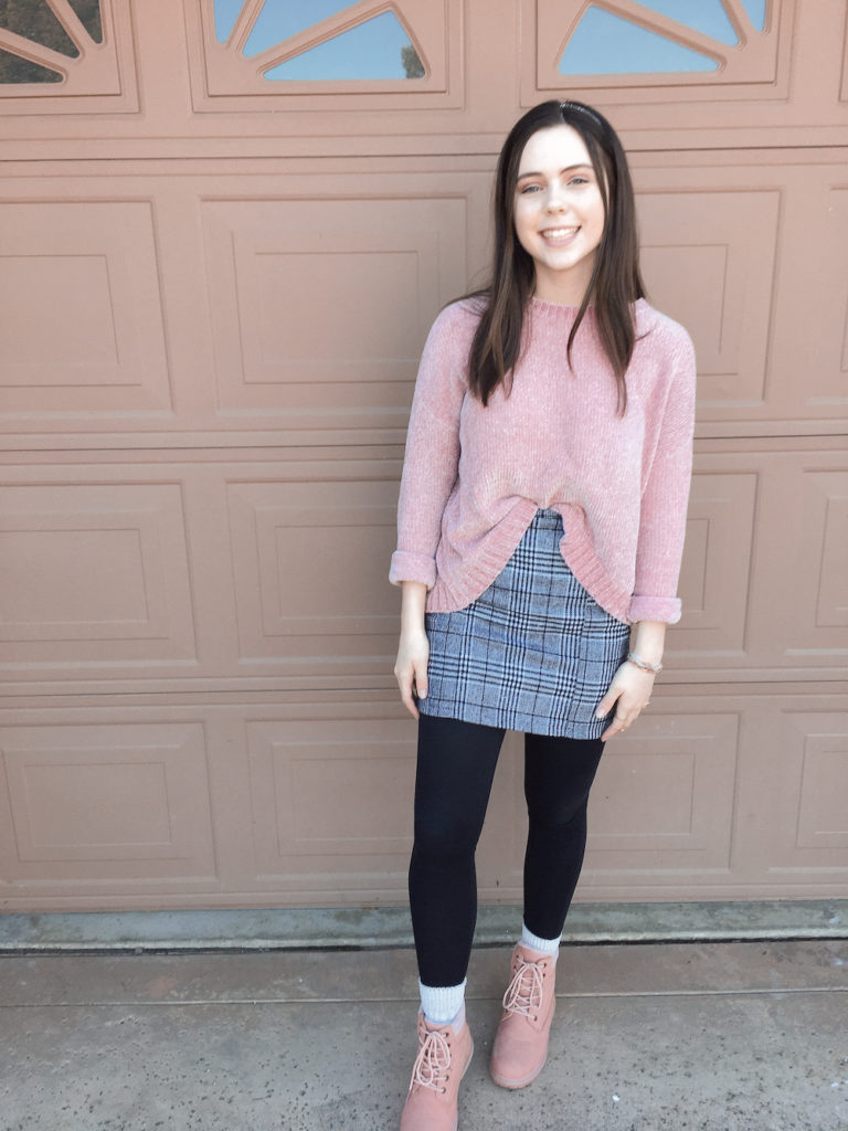 pink chenille sweatshirt with a gray plaid skirt for winter, black leggings, pink lace up boots, gold and pink bracelets, gold rings, and gray headband