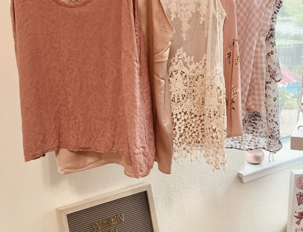 satin camisoles, shadow leopard pink cami, satin and lace champagne cami, white lace sheer tank top, pink tie front floral cami, gingham cowl neck cami, and purple and white ruffled cami displayed on a wall mounted clothing rack