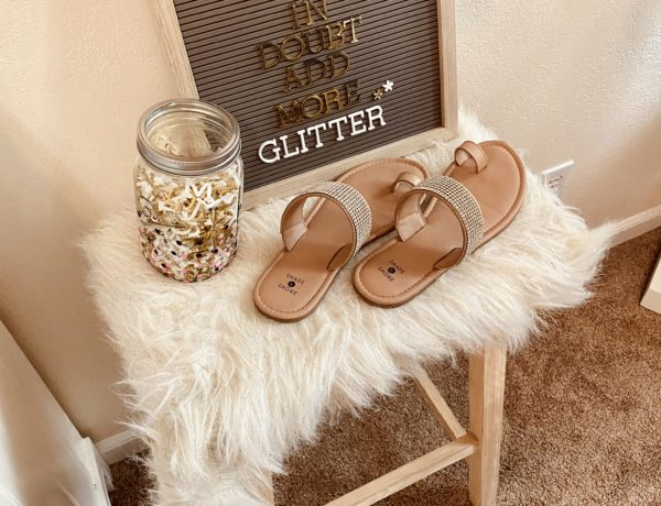 letterboard with gold letters on a white fur embellished chair and shade and shore rhinestone toe strap sandals