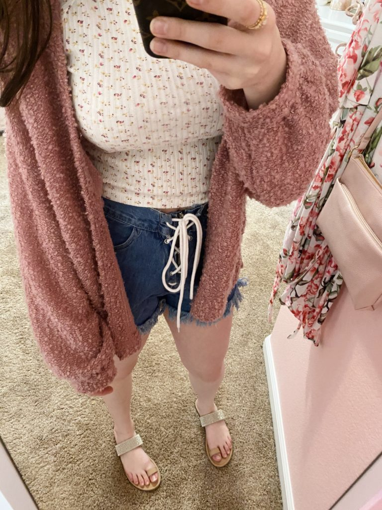 how to style a floral top, girly girl wearing a popcorn knit mauve cardigan with lace up jean shorts, sparkly sandals, and a floral tee