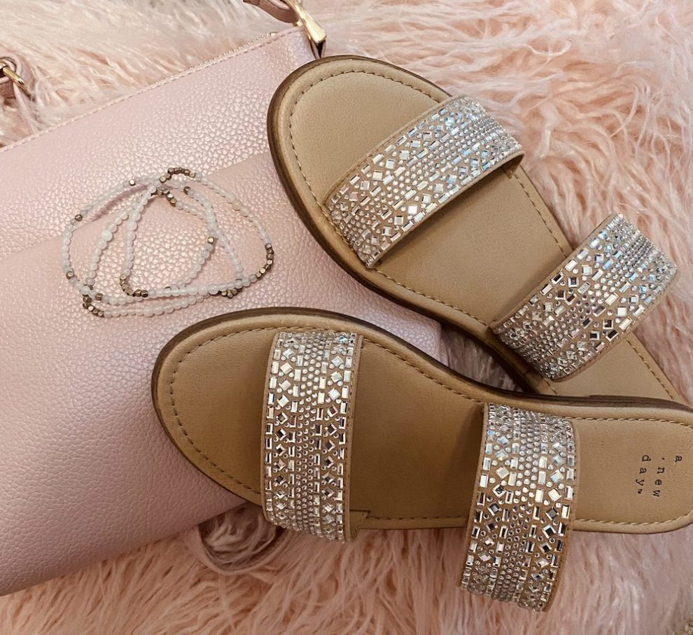 affordable must haves from target, image features embellished sandals a pink crossbody purse a pink fluffy heart pillow and a pink and gold bracelet set