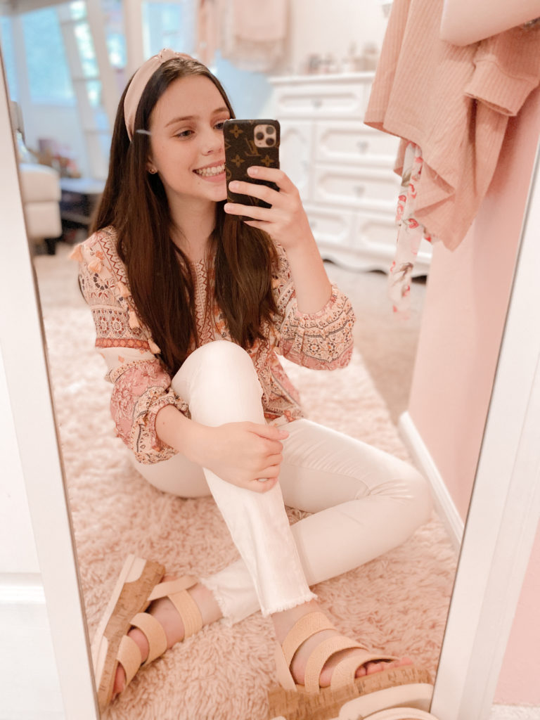 pink satin knot headband with pink and cream boho peplum puff sleeve top styled with white jeans, straw steve madden dupe espadrille sandals, gold stud earrings, and an lv case