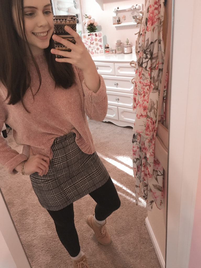plaid skirt for winter outfit, pink chenille sweater with gray plaid skirt, black leggings, and pink combat boots. very affordable and cheap outfit.