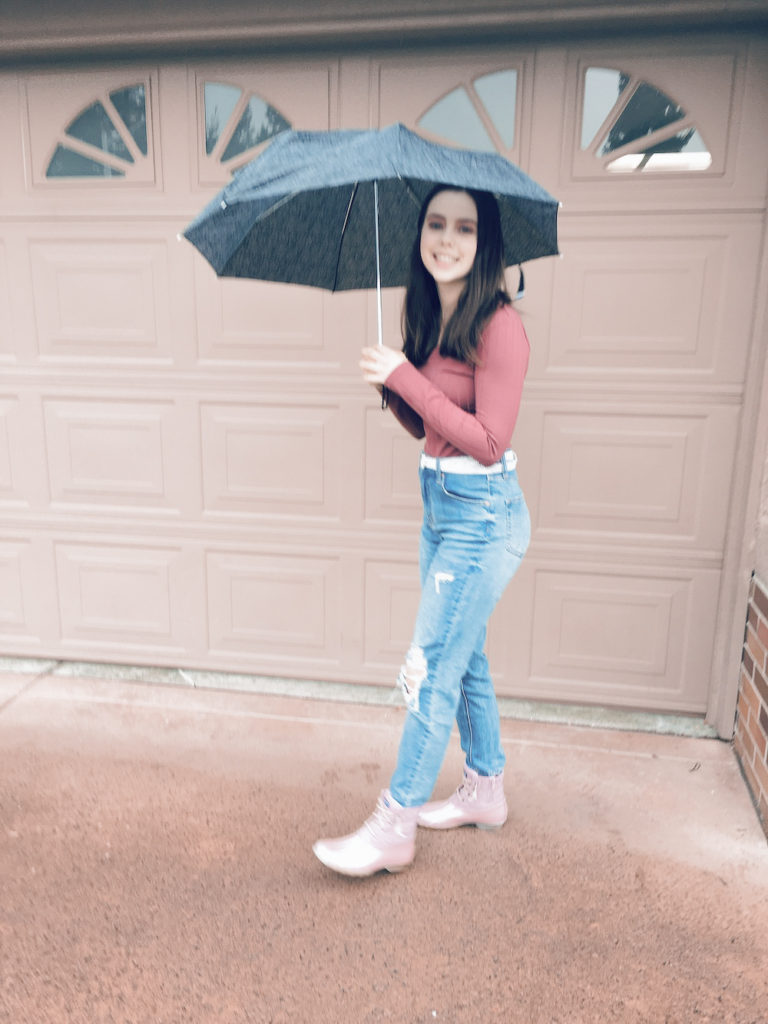 pink and girly rain boots with medium wash mom jeans, a silver sparkly belt, a floral umbrella, and a rust colored ribbed knit sweater