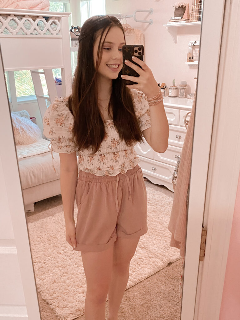 shabby chic outfit idea with a white, pink, and light green vintage floral print top with puff sleeves, ruched design, square neck, and ties styled with dusty pink casual shorts (perfect for zoom meetings), embellished sandals, victoria emerson bracelet, lauren conrad necklace, & pandora ring dupe.