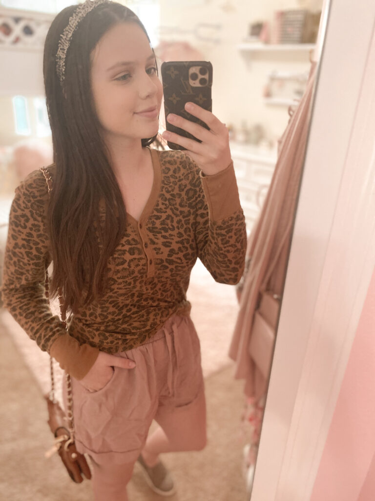 casual fall shorts outfit, dusty pink shorts with leopard waffle tee, taupe sneakers, louis vuitton phone case dupe, and black tweed headband