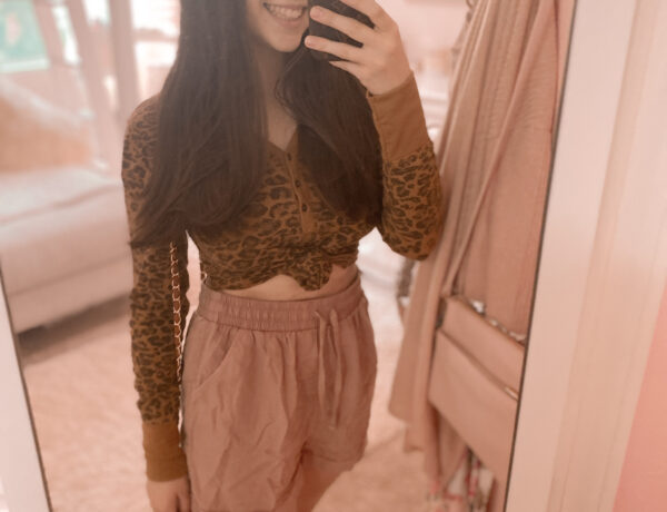 Casual Fall Shorts Outfit, sequins and satin fashion blogger wearing leopard print thermal top, dusty pink shorts, taupe slip on sneakers, a cognac crossbody purse, a louis vuitton phone case dupe, and a tweed headband