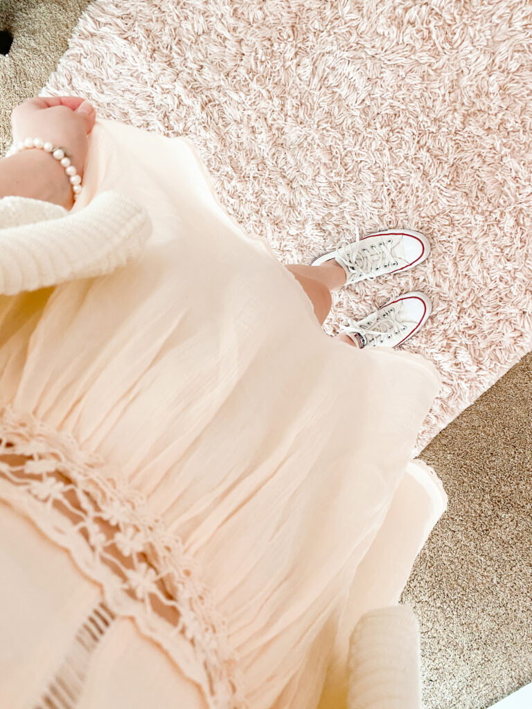 fashion blogger wearing all white monochromatic outfit with white crochet dress, white short sleeve cardigan, white low top converse, and white pearl bracelet