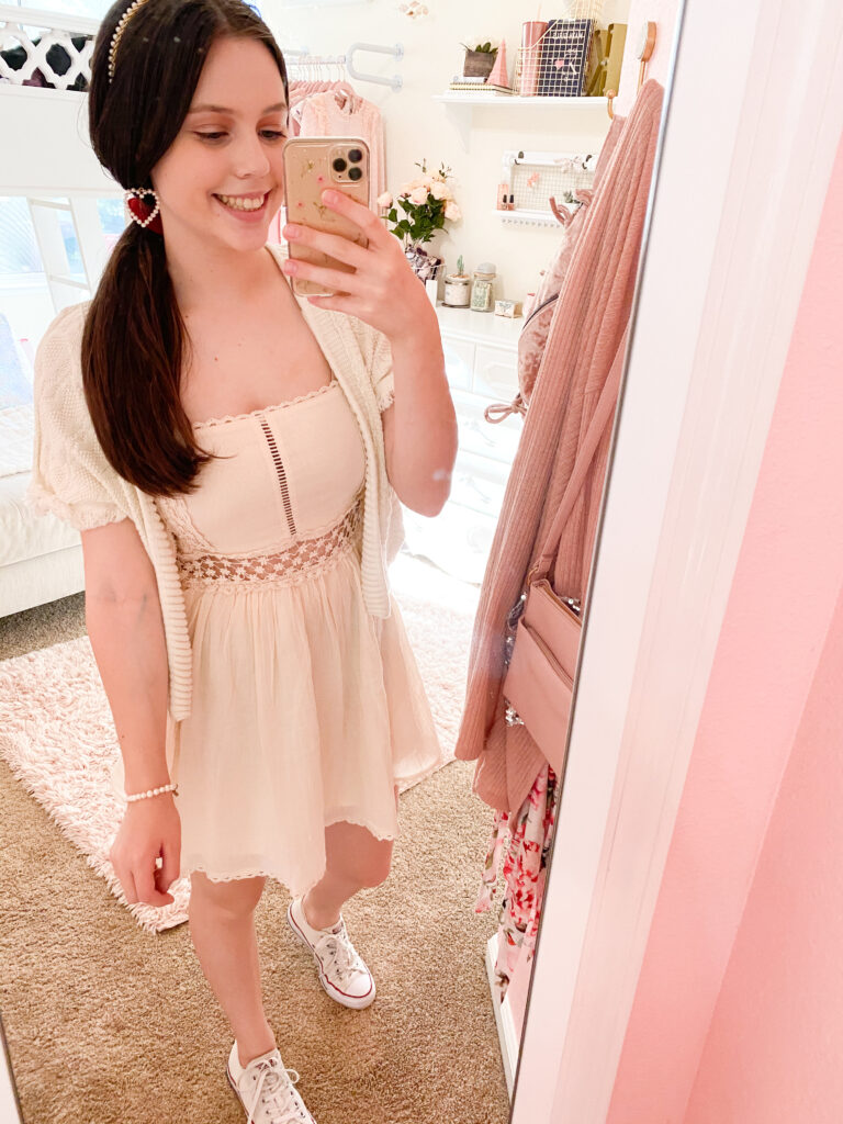 fashion blogger wearing all white monochromatic outfit with white crochet dress , white pearl headband, white pearl heart earrings, white low top converse, and white pearl bracelet
