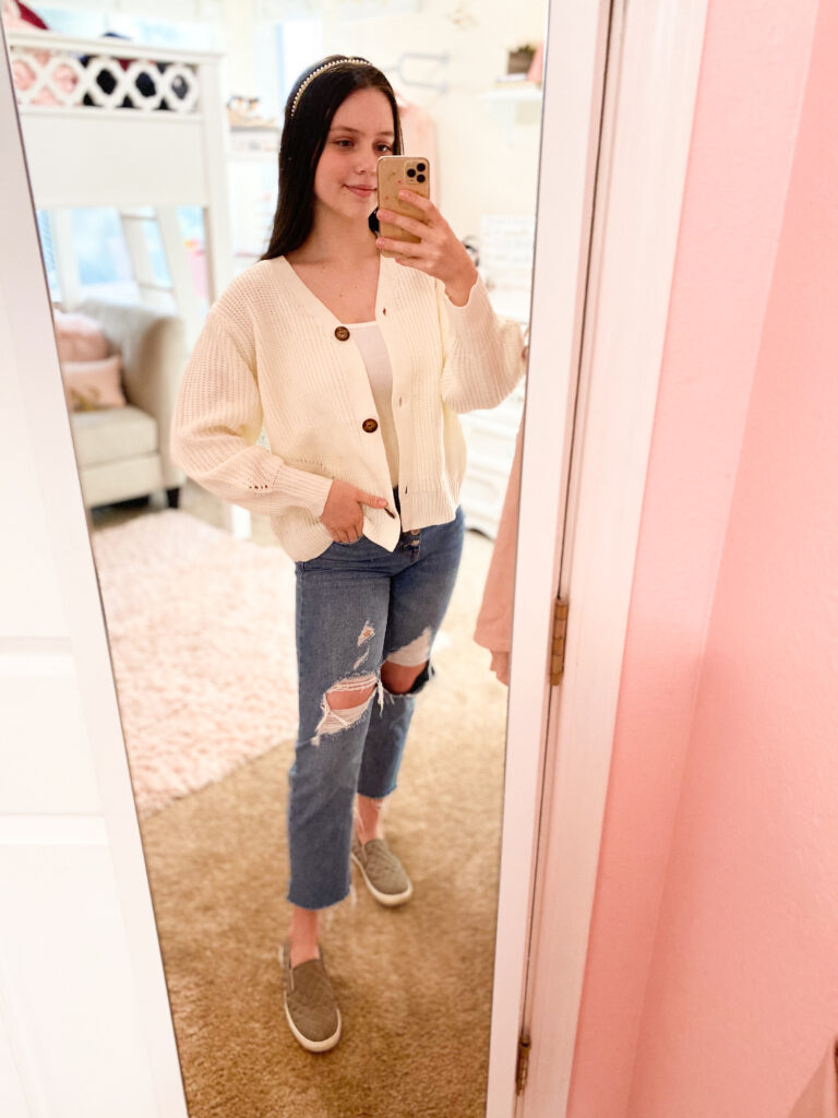 casual thanksgiving outfit idea with white oversized sweater, ripped straight leg jeans, taupe slip on sneakers, and a pearl headband to wear to a holiday party